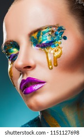 Fantasy make-up. Closeup of a beautiful woman with fantasy colorful makeup with yellow tears
