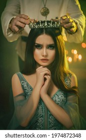 Fantasy medieval couple. Image of lovers - king and queen. hands of man put gothic crown on girl's head. Coronation of woman. vintage costume clothing. Portrait close up girl princess beauty face