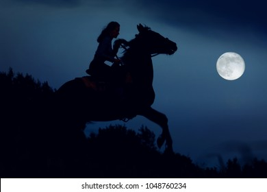 Fantasy moonlight with silhouette of the horse rearing up. Wild stallion with rider under full moon in night. Magic landscape with horseback woman riding on moonlight atmosphere background