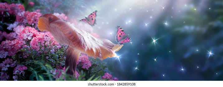 Fantasy Mushroom And Butterflies In Magical Enchanted Fairy Tale Dreamy Elf Forest With Fabulous Fairytale Blooming Pink Rose Flower On Mysterious Background, Shiny Glowing Stars, Moon Rays In Night