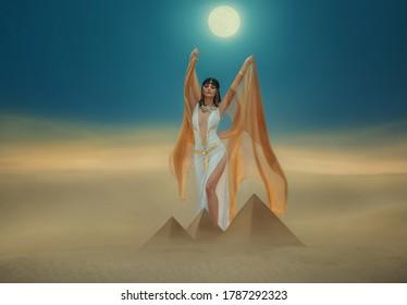 Fantasy photo. Egyptian beauty goddess Cleopatra. Woman raises hands to blue night sky, backdrop pyramid, yellow sand dune bright moon light. golden cape, white sexy dress. Black hair. queen Nefertiti