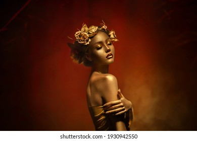Fantasy portrait of woman with golden skin. Girl goddess in wreath, gold roses, accessories. Beautiful face, steel glitter makeup. Artistic photo dark red background. Elf fairy princess. Fashion model