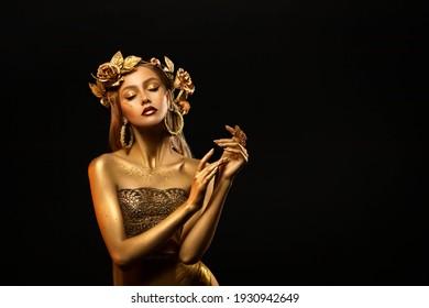 Fantasy portrait of woman, golden skin body. Girl goddess in wreath, gold roses, dress. Beautiful face steel glitter art makeup. Artistic photo dark black background. Girl princess. Fashion model pose