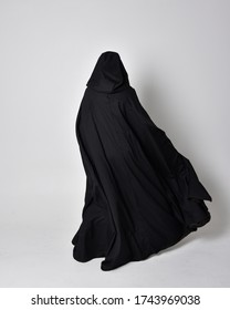fantasy portrait of a woman with red hair wearing dark leather assassin costume with long black cloak. Full length standing pose with back to the camera  isolated against a studio background.