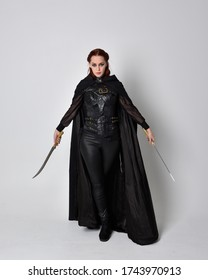 fantasy portrait of a woman with red hair wearing dark leather assassin costume with long black cloak. Full length standing pose holding a weapon,  isolated against a studio background.