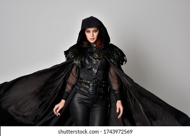 fantasy portrait of a woman with red hair wearing dark leather assassin costume with long black cloak. close up, 3/4 pose  isolated against a studio background.