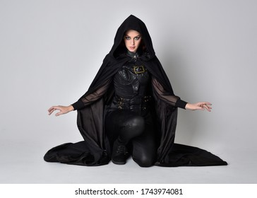 fantasy portrait of a woman with red hair wearing dark leather assassin costume with long black cloak. Full length kneeling pose  isolated against a studio background.