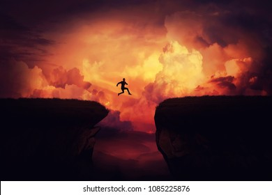 Fantasy self overcome concept as a businessman jump over a chasm obstacle above the clouds. Way to win and succes over sunset background. Achieving goals symbol.