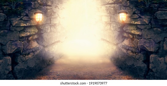 Fantasy stone dungeon cave with glowing lanterns on walls, lamp illuminate magical trail leading out from old ancient cavern towards mystical glow, scene with abandoned ruins, empty road and tunnel.