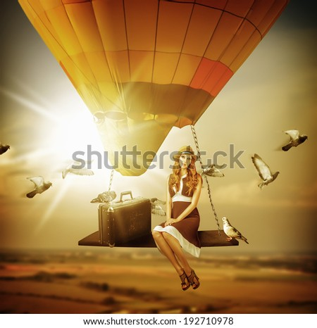 Fantasy travel. Young woman flying a balloon