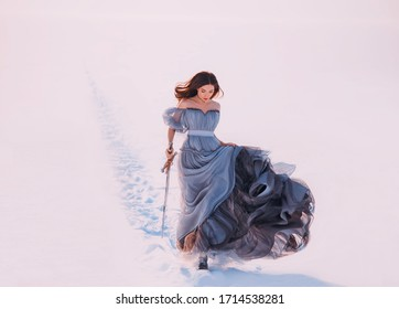 Fantasy warrior princess redhead hair elf walking winter frost white snow nature. Young beauty woman runs. queen holds hands magic blade sword. Blue silk long vintage dress fluttering fly wind motion