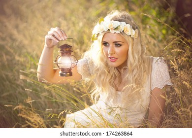 Fantasy whimsical image of beautiful woman in field holding lamp, wearing flowers in her hair