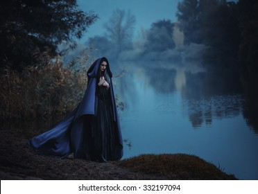 Fantasy witch in medieval old outfit cloak hood. long purple cape flies waving in wind. woman walks at night. Attractive dark queen. Blue river. image for masquerade carnival party. Gray hair strands