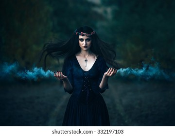 Fantasy witch in a medieval old purple outfit with a secret key around his neck. Gothic magic portrait of brunette woman. Evil scary Magician conjures smoke from her hands. Hair flutter flying in wind
