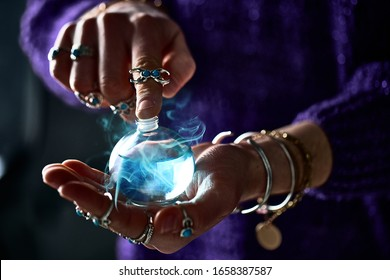 Fantasy witch wizard woman using enchanting magical elixir potion bottle for love spell, witchcraft and divination. Magic illustration and alchemy