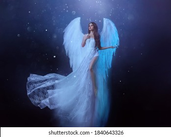 Fantasy woman angel soars in the air with white huge bird wings. Ghost girl in levitation flies. Dark night background, magical light. Lady goddess in white dress, fabric waving fluttering in motion
