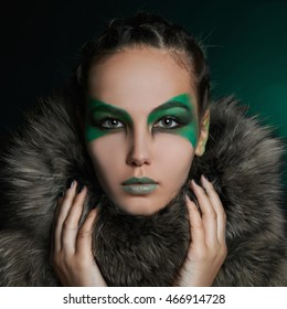 fantasy woman in fur and green make-up.fairy beautiful girl in moonlight.barbarian who lives in the woods