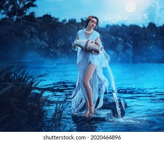 Fantasy woman Greek goddess zodiac sign Aquarius holds vintage earthenware jug in her hands and pours water into river. Background lake blue water, magic night, moon light stars. Astrology concept - Shutterstock ID 2020464896