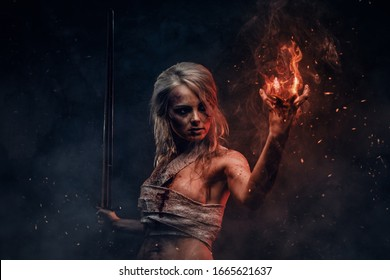 Fantasy woman warrior wearing rag cloth stained with blood and mud in the heat of battle.