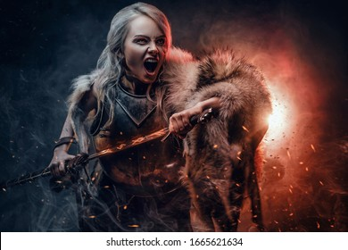 Fantasy woman wearing cuirass and fur, holding a sword and rushes into battle with a furious cry.