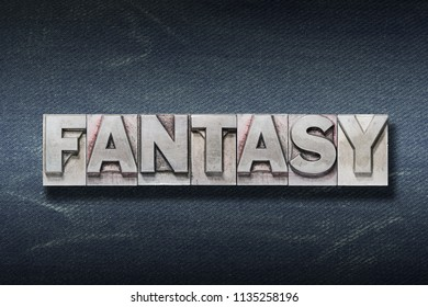 fantasy word made from metallic letterpress on dark jeans background