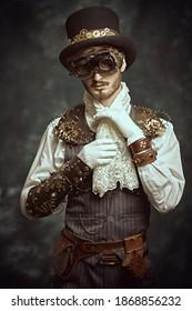 Fantasy world, adventures. Portrait of a courageous victorian steampunk man standing on a grunge background.