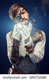 Fantasy world. Portrait of a handsome steampunk man looking at the crystal energy ball through a monocular. Dark blue background.