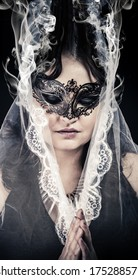 Fantasy.Veiled virgin, spirituality concept. woman with mask posing in studio.