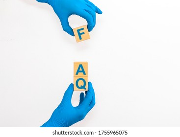 FAQ Questions and answers on wooden cube blocks in female hands in blue gloves isolated on white background