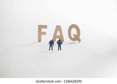 FAQ word  with Miniature people: Engineer standing infront use as business concept.