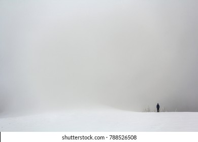 Far away lonely figure of a man standing outdoors in winter