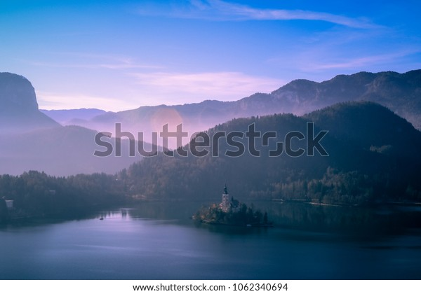 Far Lonely Island on the Lake Bled and Mountains in Gentle Fog, Slovenia