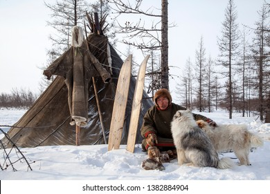 Far north of Yamal,  pasture nord reindeers, closeup portrait of Nenets at age, close-up portrait of Nenets in national clothes of the peoples of the far north, sits near the yurt with his beloved dog