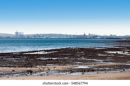 Far panorama of Belfast harbor, shipyard, Titanic quarter and Belfast Lough viewed over the beach during a low tide.