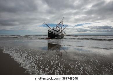 FAR ROCKAWAY, QUEENS, NY/USA - FEBRUARY 25, 2016: The scallop fishing vessel Carolina Queen III rests in heavy surf in the Atlantic ocean off Far Rockaway in the borough of Queens in New York City.