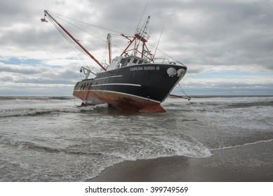 FAR ROCKAWAY, QUEENS, NY/USA- FEBRUARY 25, 2016: The scallop fishing vessel Carolina Queen III rests in heavy surf in the Atlantic ocean off Far Rockaway in the borough of Queens in New York City.