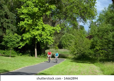 A far shot of a couple riding bicycles on a park trail together, smiling. - horizontally framed
