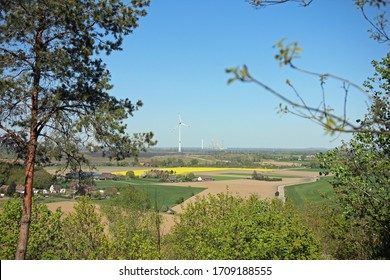 Far view from Halde Padberg in city Moers Germany over fields and farms with wind turbine and industry in the background through forest
