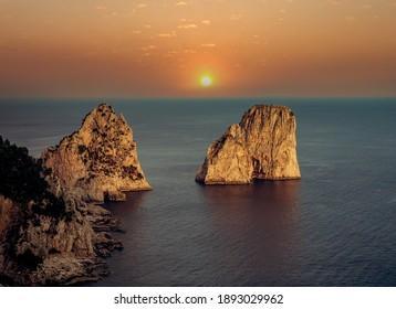 Faraglioni islands, in Capri island, Italy, with sky and clouds