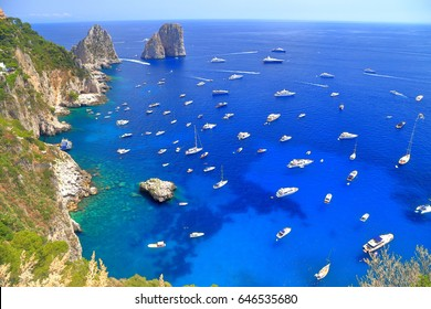 Faraglioni rocks surrounded by many leisure boats on Capri island, Italy