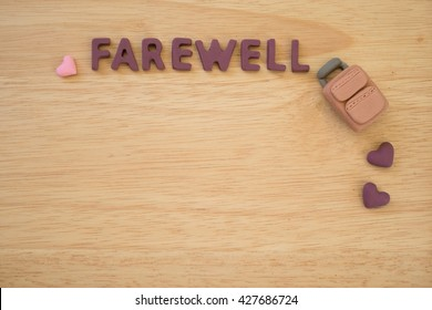 Farewell text with carry-on bag on wooden board - background - concept