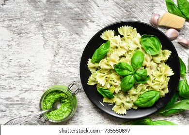 farfalle pasta with basil pesto and herbs in a plate with fork and homemade sauce in a jar. top view