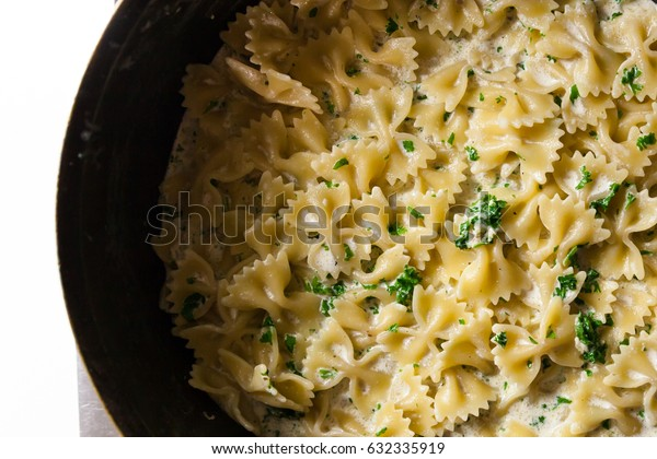 Farfalle pasta with cream sauce and herbs in a pan on the stove