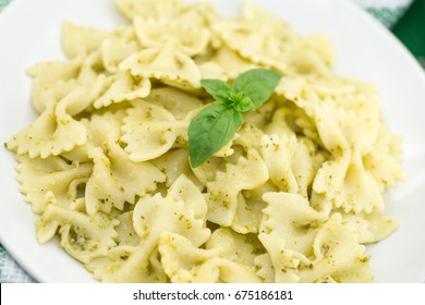 Farfalle pasta with pesto genovese (basil sauce) on rustic wooden table. Italian cuisine.