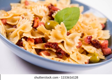 Farfalle pasta with sun dried tomato, ham and olives decorated with fresh mint