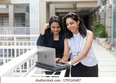 Faridabad, August 09, 2020: Two smiling  Indian women looking into a laptop in an urban corporate setting,