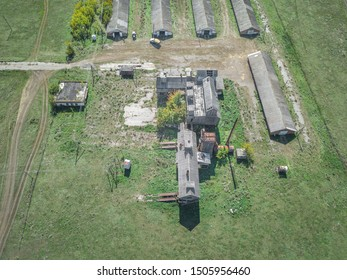 Farm barnyard with old thresh-floor surrounded by fields and meadows with green grass. Worn out agricultural buildings. Summer sunny day, aerial view, drone shot. Penza region, Russia.