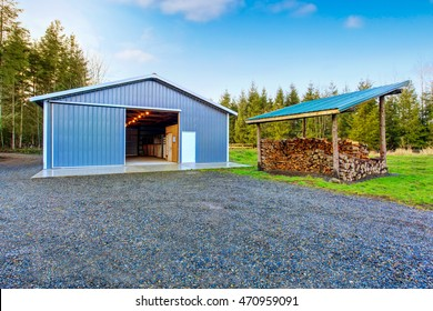 Farm blue barn shed and gravel driveway. Also dry chopped firewood logs in a pile. Northwes, USA