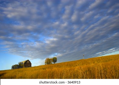 "Farm building with spectacular sky during last moments of the sunset with sign saying ""Little Hill Side Farm""on the background and prairie in the foreground"