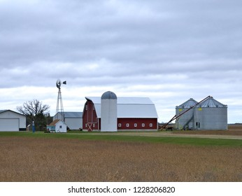 Farm buildings with active windmill on a cloudy day in Minnesota - includes barn, granary, sheds, bean field and grain auger.